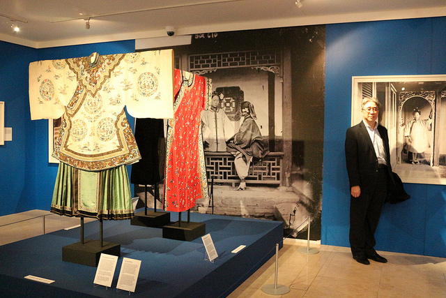 Gowns in the Women's Gallery, John Thomson Exhibition - with visitor alongside to show the scale of the large prints